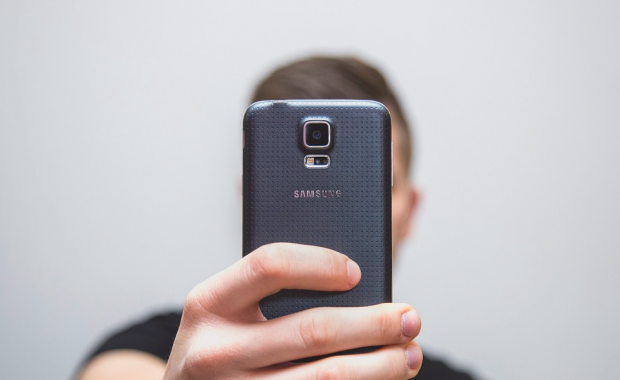 Image of person holding a mobile phone to make a call.
