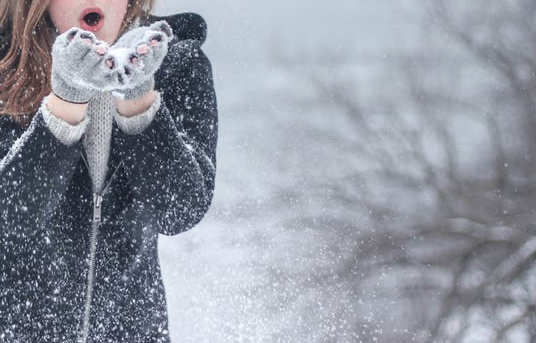 image of woman blowing snow from her hands
