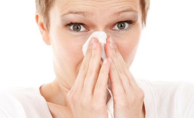 Image of woman blowing her nose due to allergies